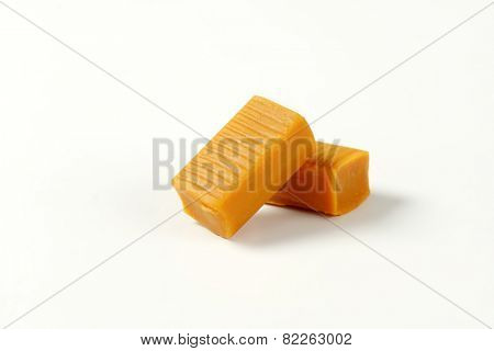 two caramel toffee candies on white background