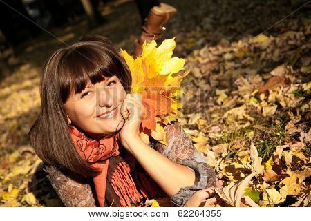 beautiful woman with autumn leaves in hand