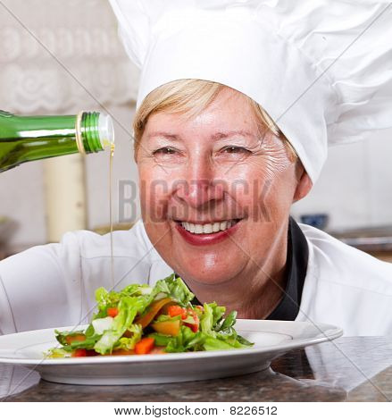chef pouring dressing on salad