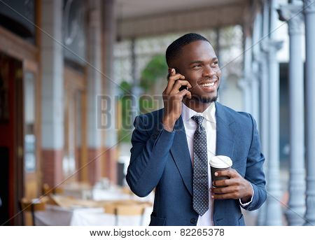 Smiling Businessman Walking And Talking On Mobile Phone