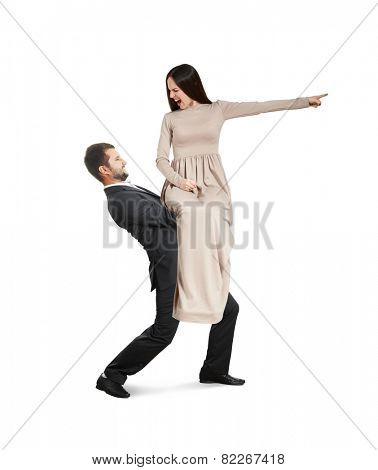 discontented young woman sitting on tired man, pointing at something and screaming. isolated on white background