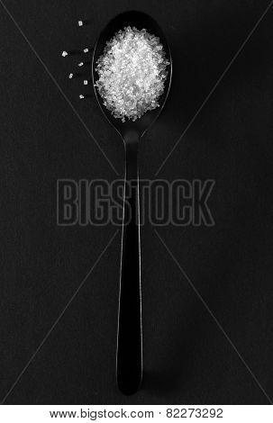 Black spoon of white sugar