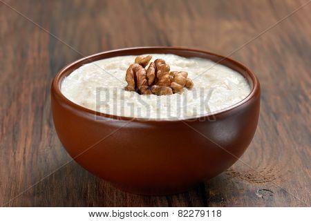 Oatmeal Porridge With Walnuts In Ceramic Bowl