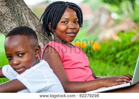 Cute African Girl Typing On Laptop Next To Brother.
