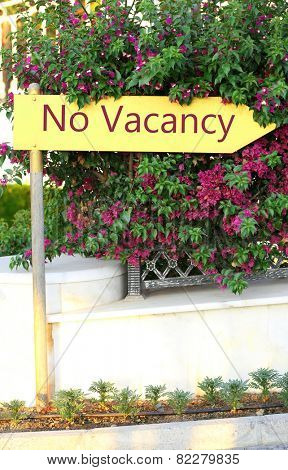 Signboard with text No Vacancy near hotel