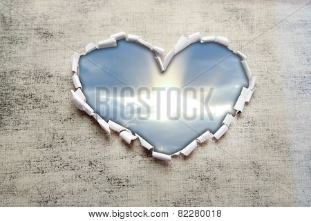 Blue sky background with clouds through heart shaped hole in paper