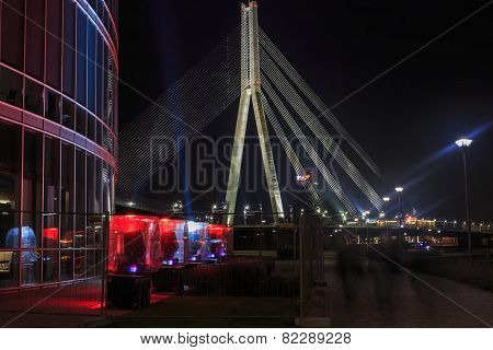 Cable-stayed Bridge Against The Backdrop Of A Fragment Of Illuminated Buildings
