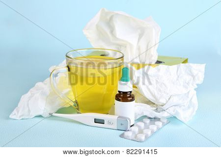 Hot tea for colds, medicine and handkerchiefs on blue background
