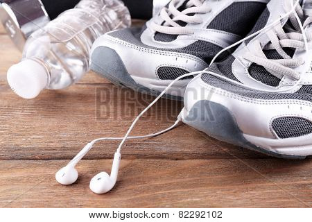 Sport shoes and bottle of water on wooden background