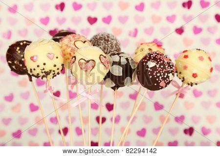 Tasty cake pops on color background