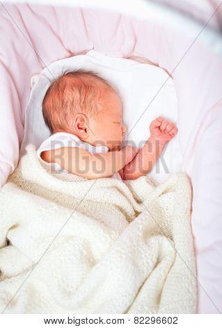 Newborn baby girl sleeping in a bassinette