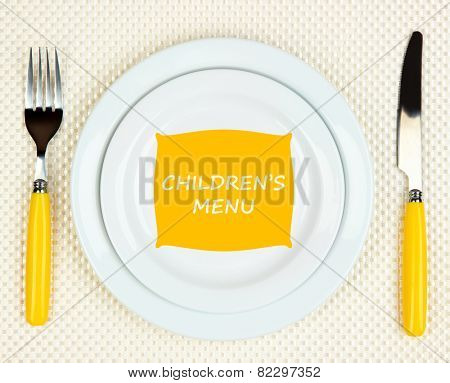 Plate with text Children's Menu, fork and knife on tablecloth background