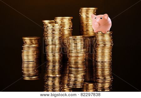 Piggy bank standing on stack of coins isolated on black