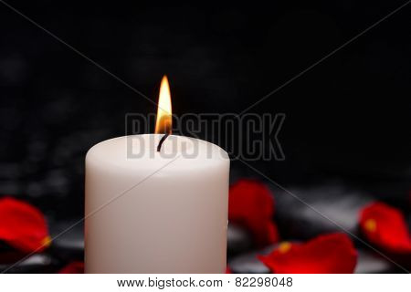 Beautiful red rose petals with white candle and therapy stones