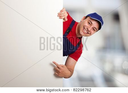 Portrait of a friendly worker pointing his finger to a blank board