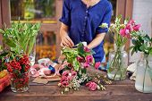 image of tied  - Female florist tying flowers up with decorative ribbon at workplace - JPG