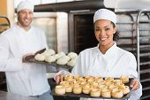 foto of trays  - Baker smiling at the camera holding tray in the kitchen of the bakery - JPG