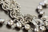 stock photo of crystal clear  - Assorted silver costume jewelry with a jumbled pile of chains with different shaped links a clear crystal bead and a necklace of round silver beads with focus to the chains.