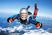 stock photo of parachute  - Skydiver falls through the air - JPG