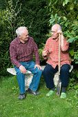 stock photo of spade  - two senior men sitting on bench in garden and discussing one is holding spade - JPG