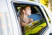 stock photo of limousine  - Bride looks out of the window a white limousine - JPG