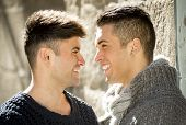 stock photo of homosexuality  - young happy attractive gay men couple smiling cuddling and having fun outdoors on street in sexual freedom and free homosexual love concept in urban background - JPG