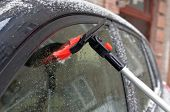 image of sleet  - Clearing of a sleet at a car window with use of a brush with a red bristle - JPG