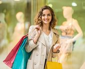 stock photo of shopping center  - Beauty woman with shopping bags in shopping mall is looking at the camera - JPG