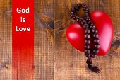 picture of prayer beads  - Heart with rosary beads on wooden background and text God is Love - JPG