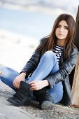 foto of jacket  - Beautiful young girl, Caucasian appearance, with dark, long, straight hair, brown eyes and beautiful dark eyebrows, wearing a striped shirt, blue jeans and black leather jacket, sitting on the street on the sidewalk