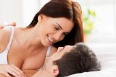 foto of cleavage  - Beautiful young loving couple lying in bed and looking at each other - JPG