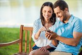picture of sitting a bench  - Beautiful young loving couple sitting on the bench together while woman pointing mobile phone and smiling - JPG