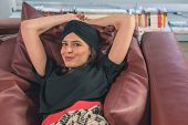 foto of turban  - Beautiful young brunette with turban posing in a bookstore - JPG