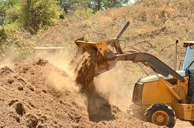 pic of backhoe  - Small backhoe moves dirt at a new commercial construction development project - JPG