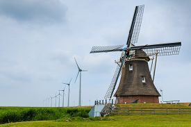 image of windmills  - Old historic dutch windmill in the foreground and new windmills generating sustainable energy in the background. Eemshaven Groningen The Netherlands.