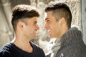 image of cuddle  - young happy attractive gay men couple smiling cuddling and having fun outdoors on street in sexual freedom and free homosexual love concept in urban background - JPG