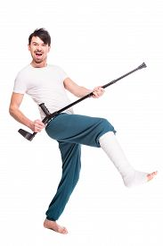 image of crutch  - Full length view of a smiling man with broken leg is using crutch and dancing isolated on white background - JPG