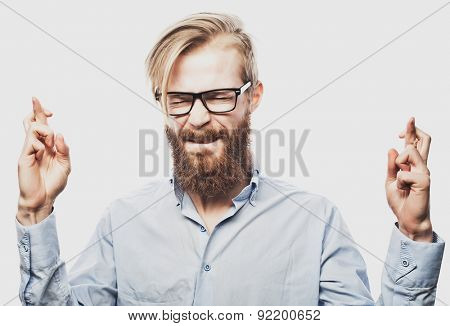 Portrait of young bearded man wearing glasses in shirt keeping fingers crossed and eyes closed while standing against white background