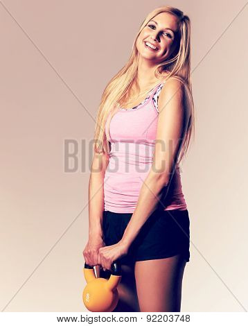 Woman Smiling And Holding A Kettlebell