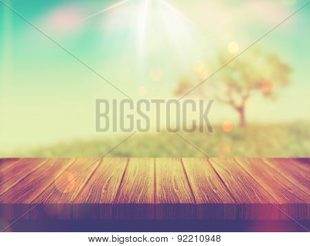 3D render of a wooden table with a tree landscape in the background with vintage effect