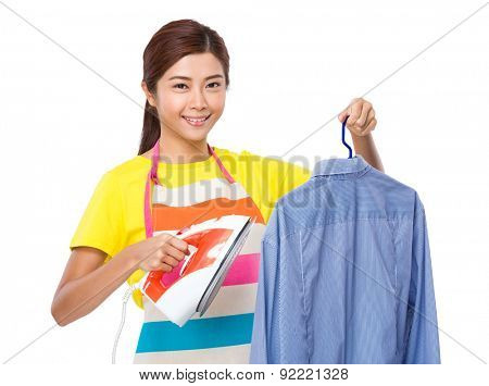 Housewife use iron for straighten of the shirt