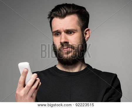 Portrait of puzzled man talking on the phone