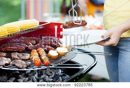 Woman Dishing Out Grilled Sausage