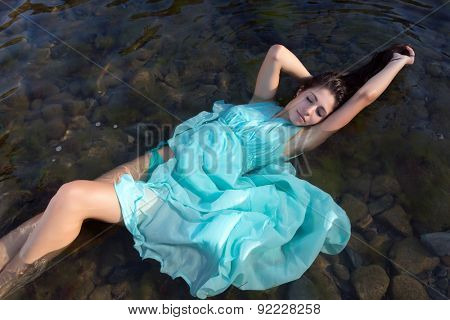 Beautiful woman in green dress floating in the shallow beach waters