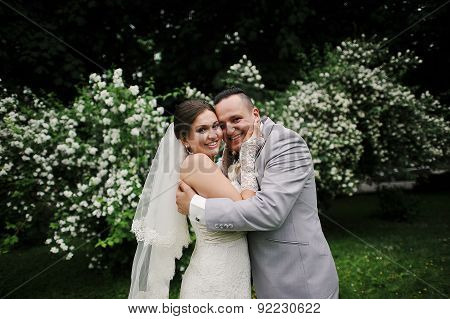 Wedding Couple In Love Near White Flowers Trees