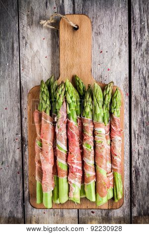 Fresh Organic Asparagus Wrapped In Prosciutto On A Cutting Board