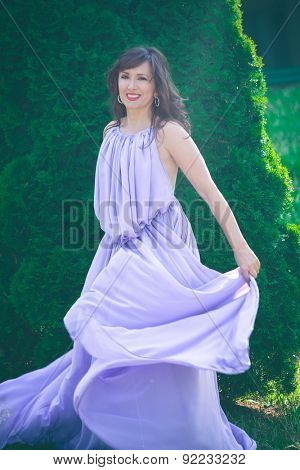 beautiful playful woman in fluttering lavender elegant dress in garden, full body shot