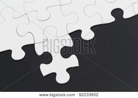 Plain white jigsaw puzzle on Black background