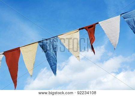 Bunting Flags Hanging Against The Blue Sky With Clouds