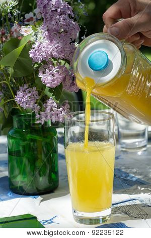 Man's Hand Pouring Orange Fruit Juice In A Glass On A Summery Garden Table With Flowers